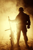 Army sniper in the fire and smoke. Army sniper with large caliber rifle standing in the fire and smoke. Backlit silhouette, toned image Stock Image