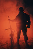 Army sniper in the fire and smoke. Army sniper with large caliber rifle standing in the fire and smoke. Backlit silhouette, toned image Stock Photo