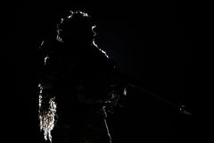 Army sniper with huge rifle. Army sniper with big rifle standing on black background. Backlit contour silhouette shot. Invisible death concept Royalty Free Stock Photo
