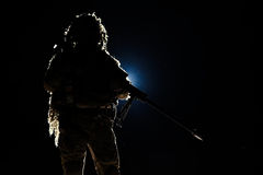 Army sniper with huge rifle. Army sniper with big rifle standing on black background. Backlit contour silhouette shot. Invisible death concept Stock Images