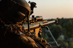 Army sniper with large caliber rifle. Special forces sniper with large-caliber rifle seeking and killing enemy. Back view sunset sky background Stock Photo
