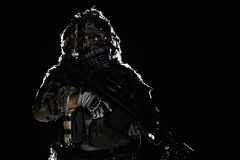 Army sniper with painted face. Army sniper with big rifle standing on black background. Face is painted with warpaint. Backlit contour silhouette shot Royalty Free Stock Photos
