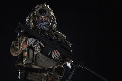 Army sniper with painted face. Army sniper with big rifle standing on black background. Face is painted with warpaint. Backlit contour silhouette shot Royalty Free Stock Image
