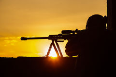 Army sniper seeking enemy. Army sniper with large-caliber sniper rifle seeking killing enemy. Silhouette on sky background. National security ensured, servicemen Stock Image