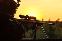 Army sniper seeking enemy. Army sniper with large-caliber sniper rifle seeking killing enemy. Silhouette on sky background. National security ensured, servicemen Royalty Free Stock Photo