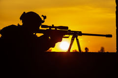 Army sniper seeking enemy. Army sniper with large-caliber sniper rifle seeking killing enemy. Silhouette on sky background. National security ensured, servicemen Royalty Free Stock Images