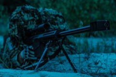 Army sniper on a stakeout. Army sniper with big rifle lying in wait in the forest at nighttime Royalty Free Stock Image