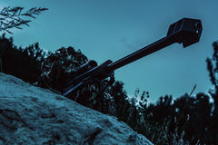 Army sniper on a stakeout. Army sniper with big rifle lying in wait in the forest at nighttime. Low angle view, diagonal shot Stock Photography