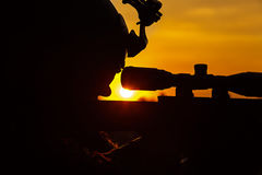 Army sniper on sunset. Special forces sniper large-caliber rifle seeking killing enemy. Closeup silhouette sky background. National security ensured, servicemen Royalty Free Stock Photos