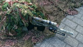 Army sniper wearing disguise camouflage suit at military show Stock Photo