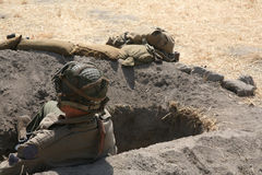 Army soldier in foxhole. Army soldier ready for combat in foxhole background Royalty Free Stock Photography
