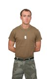 Army soldier guy. One fit attractive soldier in a brown t-shirt with dogtags half length portrait over white Royalty Free Stock Photo