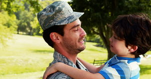 Army soldier interacting with his son in park stock footage