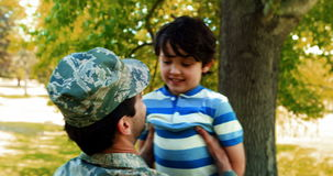 Army soldier lifting boy. In park stock footage