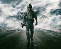 Army soldier on the road. Army soldier moving towards camera on cloudscape background Stock Images
