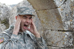Army soldier screaming in front of some ruins with copy space Stock Photography