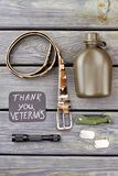 Army soldier veteran`s accessories. Military belt, bottle, flashlight, pocketknife and dog tags. Top view, flat lay Royalty Free Stock Images