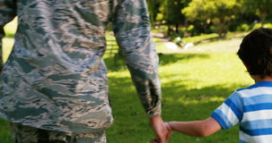 Army soldier walking with boy in park. On a sunny day stock video footage