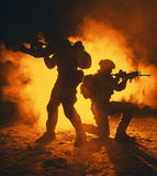 Army soldiers attacking. Pair of army soldiers attacking in the smoke. Backlit silhouette, toned image. Army storm concept Royalty Free Stock Images