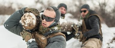 Army soldiers have hard training with huge chump wood. Army soldiers in complete equipment have hard training with huge chump wood on extreme cold and snow stock images