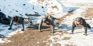 Army soldiers in complete equipment have training and doing push-ups. Army soldiers in complete equipment have hard training and doing push-ups on extreme cold stock photos