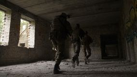 Soldiers storming the building captured by enemy. Army soldiers in full tactical gear with weapons intruding inside the building captured by enemy during stock video