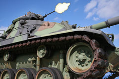 Army Tank Firing Gun. Army tank firing turret maching gun, against blue sky. Horizontal format Stock Photos