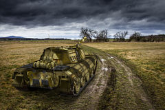 Army tank on the muddy field under the dramatic sky. Royalty Free Stock Image