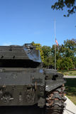 Army tank. An old army tank parked in a city park as an exhibit. Photographed fro the right rear side to show a flag flying at half mast in the background Royalty Free Stock Photography
