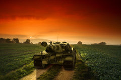 Army tank on the rural path by sunset. Royalty Free Stock Images