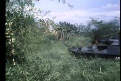 Army tanks and foot soldiers moving through tall grass stock footage