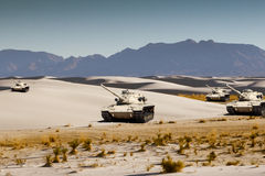 Army tanks maneuver in the white desert sand. Four United States Army war tanks doing training maneuvers in white desert sands Royalty Free Stock Photography