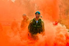Airborne troops stand in orange bombs smoke stock image