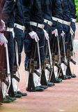 Army uniforms with machine guns in a row. Royalty Free Stock Photos