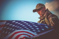 Army Veteran with USA Flag. Young Army Veteran with American Flag Closeup Photo. Army Trooper with USA Flag royalty free stock images