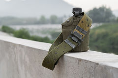 Army water canteen with a Cartridge belt at riverside. Stock Image