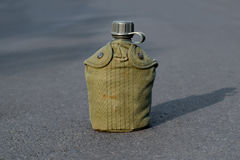 Army water canteen. With green cover on the road Stock Photo