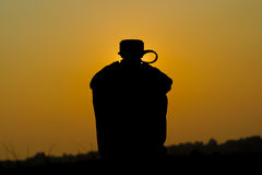 Army water canteen. Silhouette shot of Army water canteen on sunset background Royalty Free Stock Photo