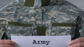 Army written on paper in hands of male soldier, military forces, closeup. Stock footage stock footage