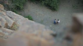 Arnés de seguridad del escalador de roca que lleva y equipo que sube