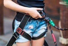 Arnés de seguridad de la muchacha que lleva en parque de la cuerda Fotos de archivo