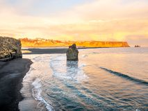 Arnardrangur rock near Vik in Iceland. Arnardrangur, known as Eagle rock, at coastline near Dyrholaey arch surrounding with heavy wave and rocky mountains at stock images