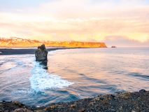 Arnardrangur rock near Vik in Iceland. Arnardrangur, known as Eagle rock, at coastline near Dyrholaey arch surrounding with heavy wave and rocky mountains at royalty free stock image