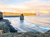 Arnardrangur rock near Vik in Iceland. Arnardrangur, known as Eagle rock, at coastline near Dyrholaey arch surrounding with heavy wave and rocky mountains at royalty free stock photo