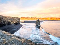 Arnardrangur rock near Vik in Iceland. Arnardrangur, known as Eagle rock, at coastline near Dyrholaey arch surrounding with heavy wave and rocky mountains at royalty free stock images