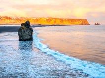 Arnardrangur rock near Vik in Iceland. Arnardrangur, known as Eagle rock, at coastline near Dyrholaey arch surrounding with heavy wave and rocky mountains at stock photos