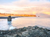 Arnardrangur rock near Vik in Iceland. Arnardrangur, known as Eagle rock, at coastline near Dyrholaey arch surrounding with heavy wave and rocky mountains at royalty free stock photography