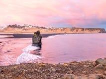Arnardrangur rock near Vik in Iceland. Arnardrangur, known as Eagle rock, at coastline near Dyrholaey arch surrounding with heavy wave and rocky mountains at stock photography