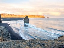 Arnardrangur rock near Vik in Iceland. Arnardrangur, known as Eagle rock, at coastline near Dyrholaey arch surrounding with heavy wave and rocky mountains at stock image