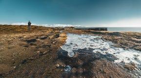 Arnarstapi,冰岛- 2018年5月:站立在一小icefield附近的年轻男性游人在与bue天空的一美好的天 免版税图库摄影